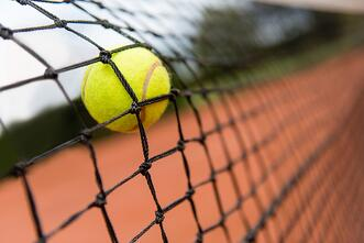 Tennis ball bouncing on the net at a clay court.jpeg